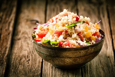 белки: С горкой деревенском миску соленых лебеда с травами, перцем и помидорами для здорового вегетарианского блюда, богатые белком и питательными веществами, стоя на старых деревянных досках