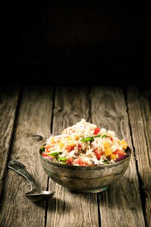 Tasty quinua sabroso cocido al vapor en un antiguo cuenco rústico con adición de chile dulce, cebolla, tomate y hierbas frescas para una comida vegetariana saludable rica en proteínas y nutrientes, con copyspace arriba Foto de archivo - 28234904