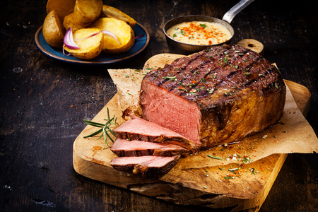 chopping board: Delicious lean rare roast beef seasoned with fresh herbs and rosemary and carved ready to serve with golden roast potatoes