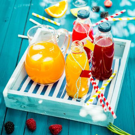 squeezed: Botellas de naranja reci�n exprimido y jugo de bayas que se coloca en una bandeja de madera sobre una mesa de picnic de color turquesa azul en dappled sol del verano Foto de archivo