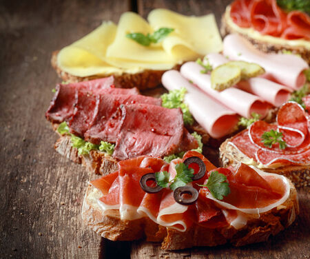 Selection of delicious open sandwiches topped with gouda cheese and assorted meats including roast beef, mortadella, ham and salami Stock Photo