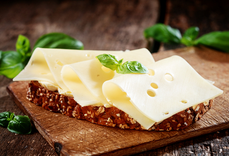 thinly: Thinly sliced gouda cheese on wholewheat bread garnished with fresh basil served on a wooden board, close up view Stock Photo