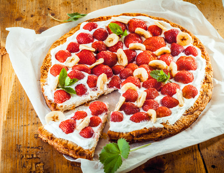 Freshly baked strawberry and banana flan with a crisp golden crust and topping of fresh berries , banana and cream garnished with peppermint on a square of white paper, high angle view photo