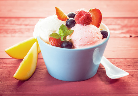 topped: Serving of vanilla and berry ice cream topped with a variety of fresh fruit including raspberries, strawberry, blueberries and sliced apple for a refreshing summer treat Stock Photo