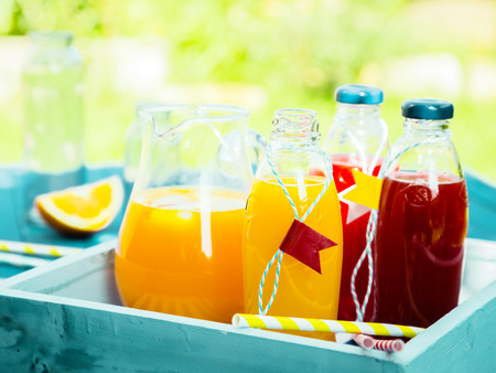 Healthy freshly squeezed fruit juice with bottles of orange citrus blend and fresh berry juice standing on a turquoise picnic table in a summer garden photo