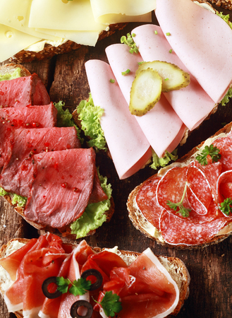 Array of tasty assorted open sandwiches on wholewheat and rye bread topped with gouda cheese, mortadella, roast beef, ham and salami Stock Photo