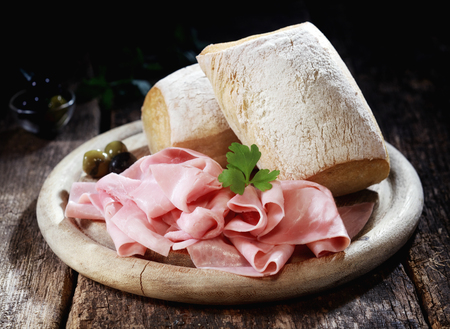 thinly: Country lunch with thinly sliced cured Bavarian ham and crusty rolls served on a wooden platter on a rustic wooden table