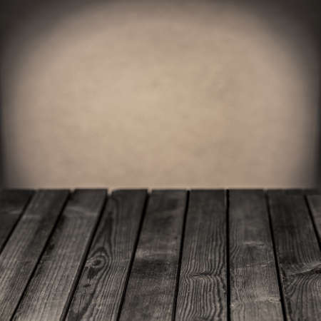 Old empty wooden rustic table in a grunge gloomy grey room with a central highlight on the blank wall behind for your placement of your food Stock Photo