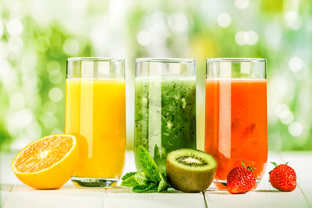 Trio of fresh healthy fruit juice blends in tall glasses on a summer picnic table outdoors with orange, kiwifruit with mint and strawberries photo