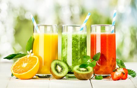 kiwi fruta: Deliciosa variedad de zumos de fruta fresca se sirve en vasos altos hechos de naranja licuado, kiwis con menta y fresas para los convites de verano saludables ricos en vitaminas Foto de archivo