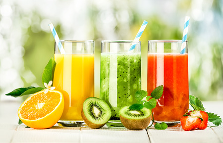 Delicious array of fresh fruit juices served in tall glasses made from liquidised orange, kiwifruit with peppermint, and strawberries for healthy summer treats rich in vitamins Banco de Imagens
