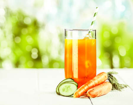 carotene: Healthy vegetable juice blend of carrot and cucumber rich in vitamins and carotene on a white wooden picnic table for a delicious summer treat Stock Photo