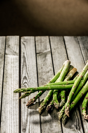 country kitchen: Freshly harvested farm fresh green asparagus spears lying on a rustic wooden table in a country kitchen, with copyspace Stock Photo