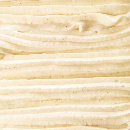 Creamy rich vanilla Italian ice cream dessert background texture arranged in decorative swirls for a cool refreshing summer treat