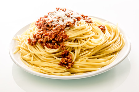 Plate of Italian spaghetti pasta with savory beef mince and grated parmesan cheese on a white background