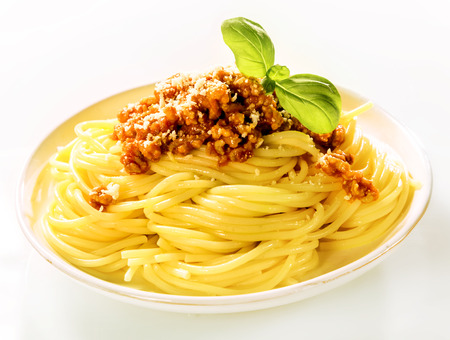 bolognaise: Plate piled high with a serving of traditional Italian spaghetti Bolognaise with fresh basil and grated parmesan cheese, side view on white