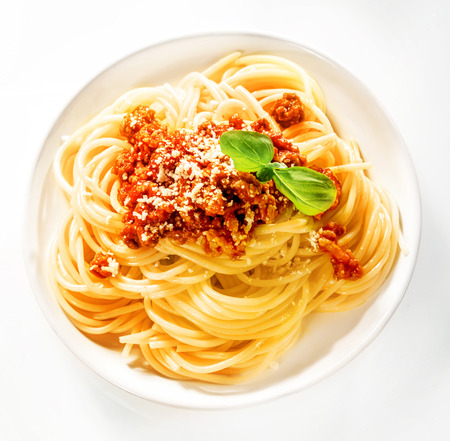 Serving of Italian spaghetti with beef and tomato sauce sprinkled with grated parmesan cheese and garnished with fresh basil leaves, view from above photo