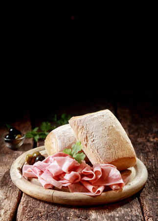 cured ham: Cured thinly sliced German ham with crusty rolls for a country lunch served on a wooden platter with copyspace, vertical format