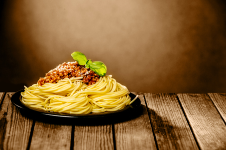 bolognaise: Tasty plate of spaghetti Bolognaise sprinkled with parmesan cheese and garnished with fresh basil served in a rustic restaurant with copyspace on a brown wall Stock Photo