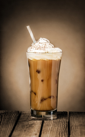 Tall glass of delicious cold iced coffee float or milkshake topped with ice cream or cream on a rustic wooden counter for a refreshing summer treat