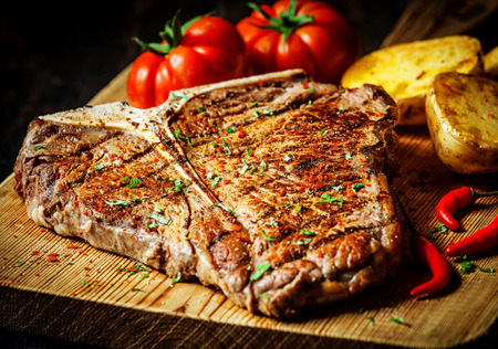 t bone: Grilled T-bone steak seasoned with spices and fresh herbs served on a wooden board with fresh tomato , roast potatoes and red hot chili peppers