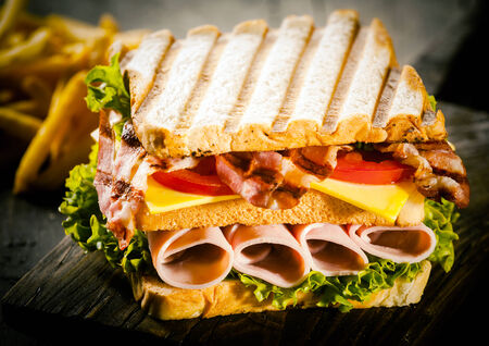chees: Delicious lunchtime snack of a toasted or grilled rolled ham and gouda cheese club sandwich with fresh lettuce and tomato, close up view