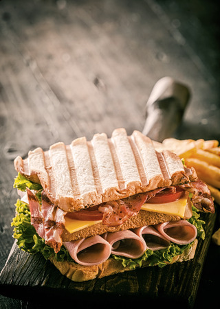 Healthy grilled ham, cheese and salad sandwich in double-decker form on toasted white bread served on an old wooden board on a rustic wooden table with copyspace photo