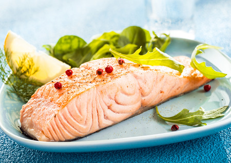 ovenbaked: Grilled fresh salmon steak showing the texture of the flesh served with a wedge of lemon and rocket and leafy green salad Stock Photo