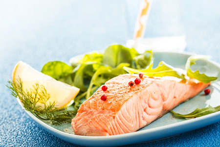 ovenbaked: Delicious succulent portion of grilled or oven-baked fresh salmon fillet served with a leafy green salad and slice of lemon for flavoring Stock Photo