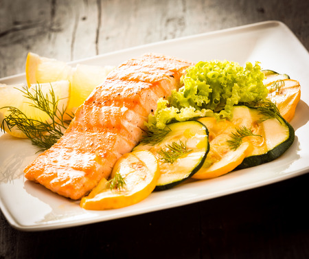 salmon dinner: Delicious gourmet grilled salmon steak with sliced roast eggplant, lettuce salad and lemon slices for a healthy seafood, dinner Stock Photo