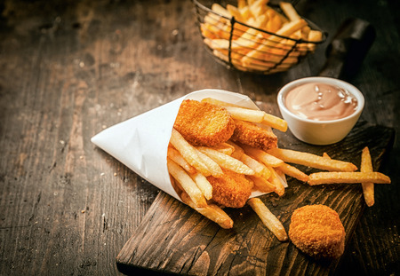 packets: Serving in a paper cone of takeaway crumbed fried fish nuggets with potato chips and a small bowl of sauce or dip on a rustic wooden table with copyspace