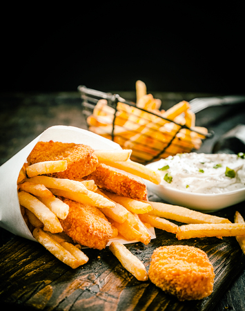 Deep fried takeaway crumbed fish portions and golden potato chips served in a disposable paper cone with tartar sauce on an old wooden table in a restaurant or fish shop