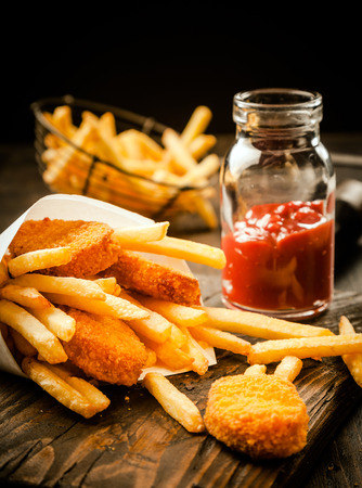 Crisp golden battered fried fish portions served with potato chips in a paper cone with a bottle of tomato ketchup in a rustic kitchen on an old wooden counter photo