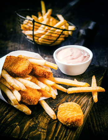 battered: Crispy golden deep fried fish and potato chips, or French fries, served with a savory mayonnaise dip on an old wooden table in a fish shop Stock Photo