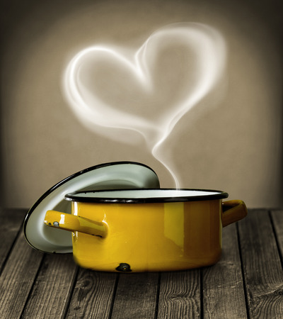 Heart shaped steam hovering in the air above a yellow enameled metal cooking pot symbolic of love on a rustic wooden kitchen counter photo