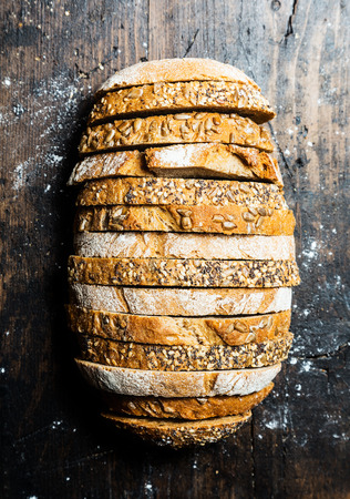 alternate: Interesting loaf of bread made up of alternate slices of brown wholewheat bread with seeds on the crust and rye bread viewed from above on an old wood surface