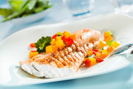 pescados y mariscos: Delicioso filete de pescado a la parrilla saludable servido en un plato con una ensalada fresca de colores para una cena de sabroso marisco