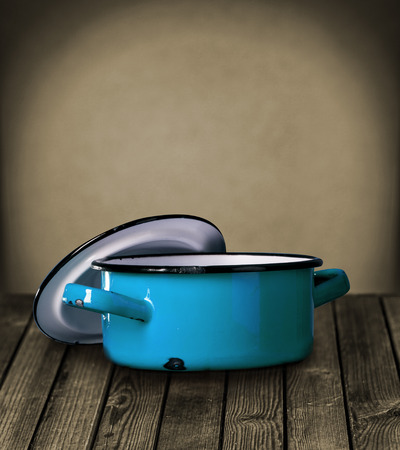 Old blue enameled pot and lid standing on a rustic wooden table against a dark grey wall with a vignette and copyspace photo