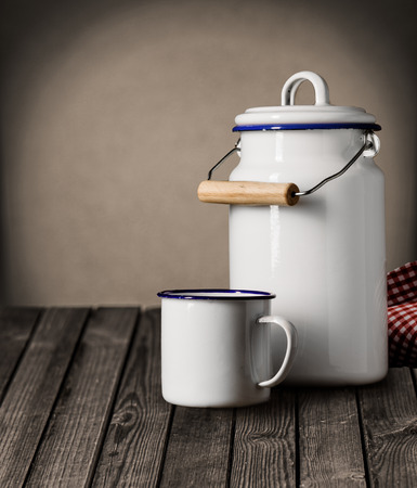 Enameled white tin mug and kitchen storage canister with a lid and handle standing on an old grunge wooden counter with copyspace on the wall behind photo