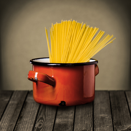 Uncooked Italian spaghetti in a colorful red enameled pot standing on a rustic wooden kitchen counter while preparing a tasty Italian pasta meal photo