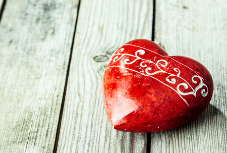 heart of stone: Red heart shaped stone on wooden surface
