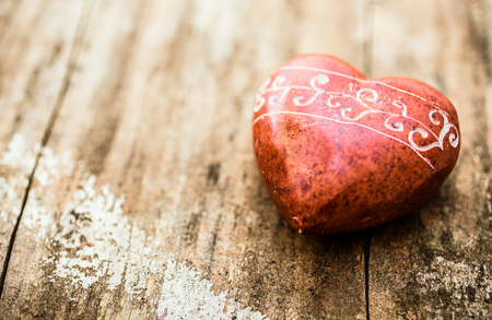 heart of stone: Red stone shaped like a heart with carvings on a wooden surface. Stock Photo