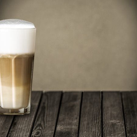 latte macchiato: Glass of aromatic macchiato Italian coffee with rich full roast espresso topped with foamy milk and served on a rustic wooden table at a cooffee house or restaurant, with copyspace