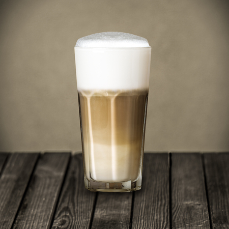 latte macchiato: Glass of rich foamy Italian Macchiato coffee made from freshly brewed aromatic espresso topped with foaming milk standing on a rustic wooden table at a country restaurant Stock Photo