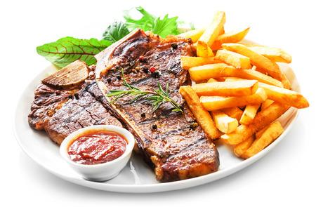 Mals gegrilde porterhouse of T-bone steak geserveerd met krokant gouden friet en verse groene kruiden salade vergezeld van een BBQ of tomatenketchup saus Stockfoto