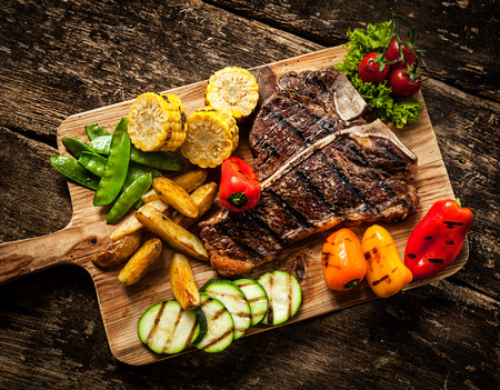 Delicious steakhouse porterhouse steak and colorful fresh roast vegetables with mangetout peas, corn, zucchini, bell pepper, potato and tomato on a wooden board, view from above