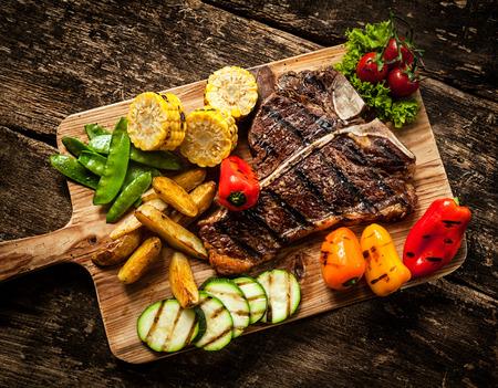 Heerlijk steakhouse entrecôte en kleurrijke vers geroosterde groenten met peulen, maïs, courgette, paprika, aardappel en tomaat op een houten plank, bekijken van boven Stockfoto