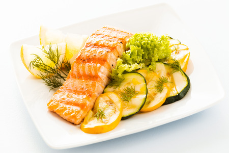 Salmon steak with sliced zucchini and courgette, lettuce and lemon garnished with fresh dill for a tasty seafood platter or appetizer photo