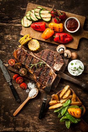Gezonde spreiding met t-bone of entrecôte geserveerd met een assortiment van gezonde geroosterde groenten en hartige dips op een rustieke houten tafel in een landelijke keuken Stockfoto