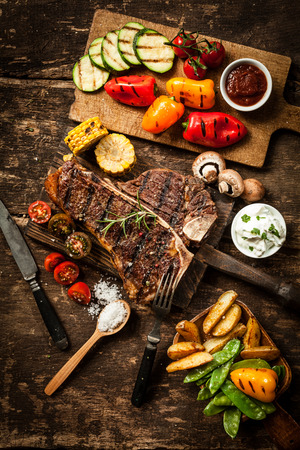 t-뼈 또는 비프 스테이크와 건전한 확산은 국가 부엌에서 소박한 나무 테이블에 건강한 볶은 야채와 짭짤한 딥의 구색을 제공합니다